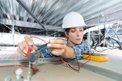 Female electrician installing cables. Female electrician installing of cables Royalty Free Stock Photo