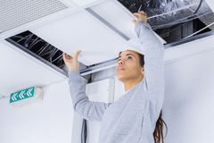 Female electrician installing electric device in ceiling. Female Stock Photo