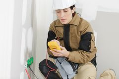 Female electrician installing electrical socket on wall. Female Royalty Free Stock Photo