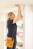 Female Electrician Installing Light. Fitting In Home Stock Photos