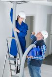 Female electrician installing ventilation pipese in ceiling. Ventilation Stock Image