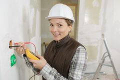 Female electrician installing wall socket. Female electrician installing a wall socket Royalty Free Stock Image