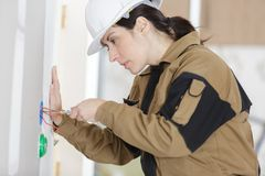 Female electrician installing wall socket. Female electrician installing a wall socket Royalty Free Stock Images