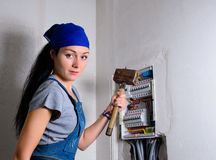Female electrician. With a mallet in her hand standing in front of open fuse box Royalty Free Stock Image