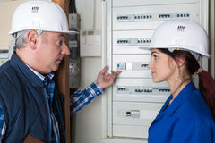 Female electrician and master. Female electrician and her master Stock Image
