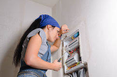 Female electrician with open fuse. Low angle view of a female electrician with a screwdriver in her hand standing in front of open fuse box Royalty Free Stock Photos