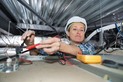 Female electrician reaching to test light with multimeter. Test Stock Photography
