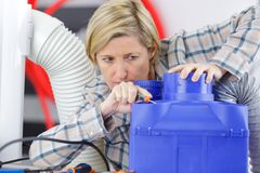 Female electrician reapiring machinery. Construction Royalty Free Stock Images