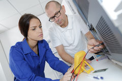 Female electrician repairing radiator helped by professor. Female electrician repairing a radiator helped by professor Royalty Free Stock Photos