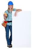 Female electrician standing with advertising. Board Royalty Free Stock Photography