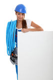 Female electrician. Stood by advertising panel Stock Photography