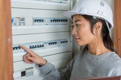 Female electrician switching off panels. Female electrician switching off the panels Stock Photo