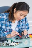 Female electrician testing elctronic part. Young Stock Photography