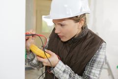 Female electrician testing wall socket. Female electrician testing a wall socket Royalty Free Stock Photo