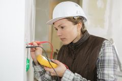 Female electrician turning to smile. Female Royalty Free Stock Photography