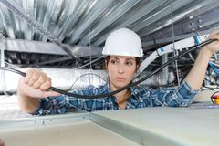 Female electrician wiring in building ceiling. Woman Royalty Free Stock Image