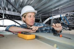 Female electrician wiring inside ceiling. Electrician Royalty Free Stock Photo