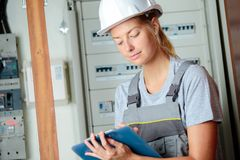 Female electrician writing on clipboard. Electrician Stock Photography