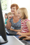 Female Elementary Pupil In Computer Class With Teacher Royalty Free Stock Photos