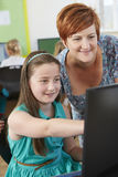 Female Elementary Pupil In Computer Class With Teacher Stock Photography