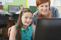 Female Elementary Pupil In Computer Class With Teacher. Elementary Pupil In Computer Class With Teacher Stock Photo