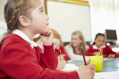 Female Elementary Pupil Working At Desk Royalty Free Stock Images