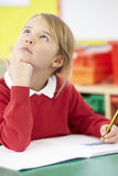 Female Elementary Pupil Working At Desk Stock Images