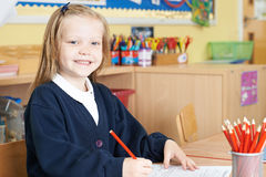 Female Elementary School Pupil Working At Desk Stock Photo
