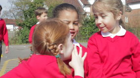 Female Elementary School Pupils Whispering In Playground. Three schoolgirls whisper together as boys play in background. Shot on Canon 5d Mk2 with a frame rate stock video