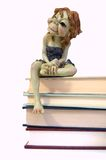 Female elf on books. A small, ceramic, female elf sitting on a stack of books Royalty Free Stock Photos