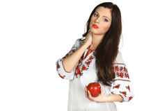 Female in embroidery chemise holding red apple Stock Photo