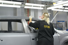 The female employee of checking department checks quality of pol. Ishing of a body of the car. Car assembly enterprise Stock Image