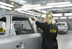 The female employee of checking department checks quality of a r. Ikhtovka of a body of the car. Car assembly enterprise. Kaliningrad, Russia. 16.09.2014 Stock Photo