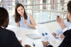 Female employee discuss paperwork issue with colleagues at brief. Young female employee talk on paperwork issues during company meeting with colleagues royalty free stock photography