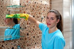 Female employee doing cleaning in bathroom. Cleaning company concept. Portrait of charming young female employee of cleaning company in rubber gloves wiping stock photography