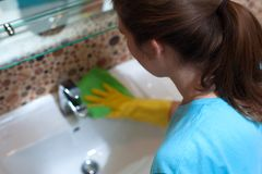 Female employee doing cleaning in bathroom. Young female employee of cleaning company in rubber gloves wiping sink in bathroom royalty free stock photos