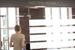 Female employee enter meeting room ready for presentation. Female employee enter company meeting room having paper report or corporate documents in hands stock photography