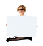 Female employee holding white blank banner ad. Seated on floor, legs-crossed Royalty Free Stock Photography