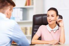 Female employee looks at her partner seductively Stock Photos