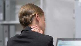 Female employee massaging painful neck, sedentary lifestyle result, back view