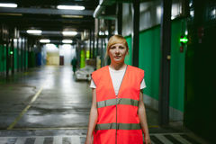 Female employee in an orange robe vest in the working space of a production facility Royalty Free Stock Photo