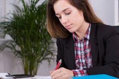 Female employee preparing the report. Panoramic view of an female employee preparing an important report Stock Photo