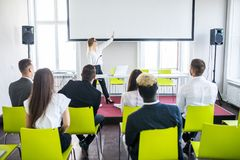 Female employee raise hand asking question to businesswoman making flipchart presentation. Young woman answering during stock photo