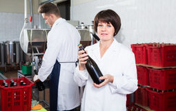 Female employee showing wine bottle at sparkling wine factory. Happy adult female employee showing wine bottle at sparkling wine factory stock image