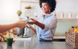 Female employee taking payment from customer Royalty Free Stock Photos