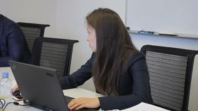 Female employee working with laptop, talking to colleague at modern office. Female employee working with laptop, talking to colleague at modern office stock video