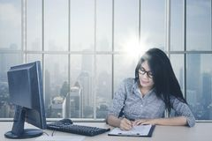 Female employee writing on the paperwork. Picture of a female employee writing on the paperwork by using a pen while sitting by the window. Shot in the office Stock Photos