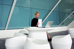 Female employer watching news via laptop computer after finished analyzing financial documents Royalty Free Stock Image