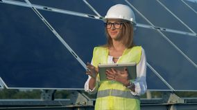 Female energetics specialist is working near a solar array and smiling. 4K stock footage