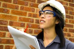 Female engineer. Studying plans on worksite